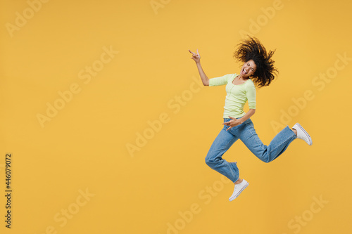 Fototapeta Full size body length happy african american young woman 20s wears green shirt jump do guitar gesture keep eyes closed isolated on yellow background studio portrait