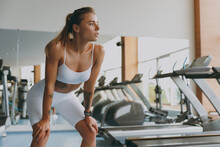 Young Tired Strong Skinny Sporty Athletic Sportswoman Woman In White Sportswear Warm Up Training Near Treadmill Stand Lean On Knees Look Aside Breathing In Gym Indoor Workout Sport Motivation Concept.