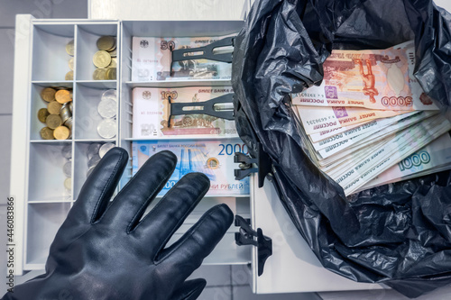Fotografia Robber's hand in black glove stealing cash rubles (Russian money) from cashbox a