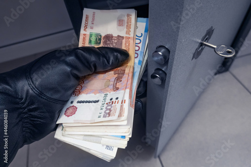 Robber's black-gloved hand pulls out wad of Russian rubles money from safe Fototapeta
