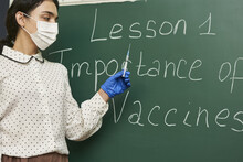 Teacher Wearing A Facemask And Teaching About The Importance Of Vaccines To The Class