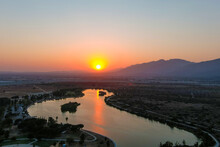 A Stunning Aerial Shot Of A Sunset Over The Lake Surrounded Majestic Mountain Ranges And Lush Green Trees And Grass At Santa Fe Dam Recreation Area In Irwindale, California