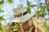 Tam, gdzie rosną poziomki. Dziewczyna w kapeluszu zajada leśne poziomki, w słoneczny letni dzień..