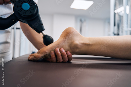 Fototapeta Close-up of masseur rubbing woman foot with massage percussion device in rehab c