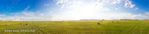 Fotografie, Obraz Russian summer panoramic landscape with sunny green meadows with mown hay, haystacks and awe sky with clouds