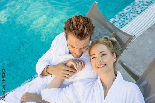 Fotografia Attractive couple lying on the sunbeds wearing bathrobe by the indoor hotel swim