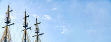 The Masts Of The Old Ship On The Background Of The Blue Sky. The Concept Of Travel Copy Space And Banner