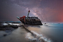 Boat Crashes In The Sea And Milky Way. Climate Change.