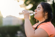 Dehydrated Woman. Water Thirst. Nutrition Wellness. Body Healthcare. Side View Portrait Of Obese Overweight Drinking Lady In Defocused Copy Space Sunset Background.
