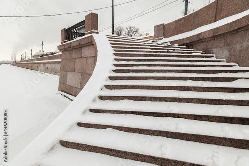 Slika na platnu Snow-covered granite stairs on the embankment of the Neva River
