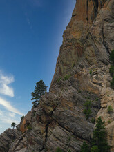 High Mountain Of A Geologic Formation With A Small Tree Growing On The Cliffside
