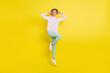 Leinwandbild Motiv Full length body size photo of cheerful model jumping showing v-sign isolated bright yellow color background