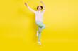 Leinwandbild Motiv Full length body size photo of cheerful model jumping up smiling waving hands isolated vivid yellow color background