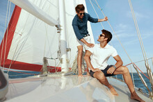 Young Male Friends Resting On Yacht In Sea