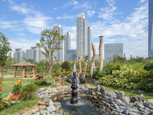 Skyline Of Songdo In South Korea, Wooden Totem Poles Called Jangseung In A Park