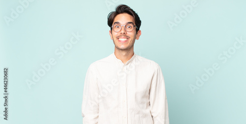 Fotografie, Obraz hispanic handsome man looking happy and goofy with a broad, fun, loony smile and