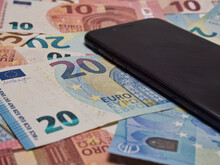 Closeup Shot Of A Pile Of Ten And Twenty Euro Banknotes And A Smartphone