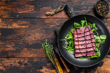 Grilled Teriyaki Tuna Steak Salad With  Arugula And Spinach. Dark Wooden Background. Top View. Copy Space