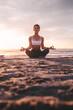 Leinwandbild Motiv Woman meditating in lotus pose during sunset