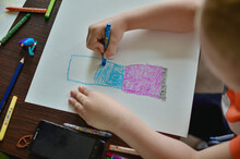 The Child Draws With Colored Pencils On Paper.