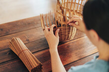 Woman Weaves Basket Of Paper Tubes On Wooden Table