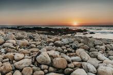 Mesmerizing Sunset Above The Sea Seen Through Coastal Rock