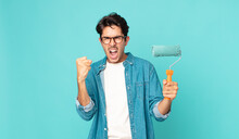 Young Hispanic Man Shouting Aggressively With An Angry Expression And Holding A Paint Roller