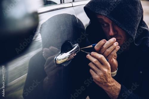 Obraz na plátně A car thief opening a car door with a lockpicer.