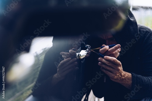 Fotografie, Obraz Masked thief opening a car door with a lockpick.