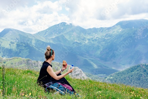 Fotografie, Obraz A blonde hiker sits on the grass, eats and drinks water, resting in the beautiful Polish mountains