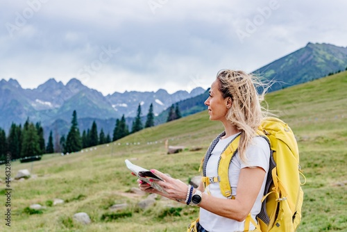 Obraz na plátně Adventurous blonde woman navigating in with a topographic map in the beautiful polish mountains