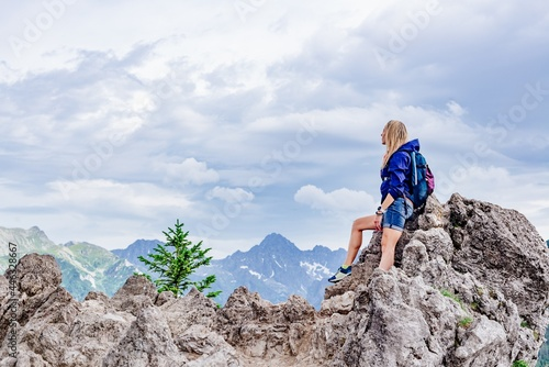 Fototapeta A blonde tourist is sitting on a rock in the beautiful Polish mountains