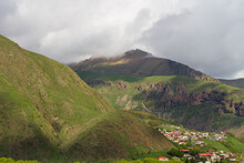 A Small Village Is Located At The Foot Of Beautiful Green Mountains, On Top Of Which Are Clouds, Georgia