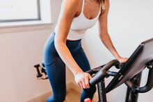 Close Up Of Woman Riding Exercise Bike In Home Gym