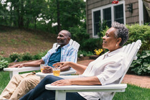 Side View Of Retired Couple Relaxing With Iced Tea In Chairs At Home