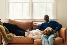 Couple Laughing With Joy While They Spend Time On The Couch Together