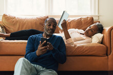 Husband Showing Wife Text On Cell Phone While They Relax Together