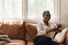 Grandmother Laughing While She Reads A Text From Grandkids At Home