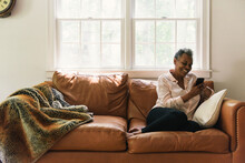 Retired Woman Enjoying An Afternoon Reading On Phone In Home