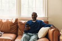 Man Taking A Moment To Relax And Read From His Cell Phone On The Couch