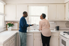 Couple Working Together To Do The House Chores And Washing Dishes