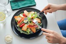 Woman Eating Tasty Caesar Salad At Table In Restaurant, Closeup