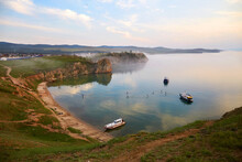 Lake Baikal, Olkhon Island On A Summer Evening. View Of The Khuzhir Bay Near The Shaman Rock. Boats And Yachts With Tourists Are Resting In The Bay. A Lot Of People Ride Sup Boards.