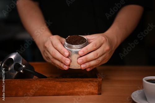 Fotografie, Obraz Barista holding moka pot with  ground coffee in dark room.