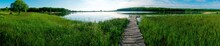 Panorama Of A Wooden Path For Fishermen. Green Thickets On The Shore Of The Pond.