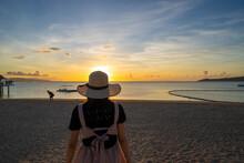 石垣島の夕日のフサキビーチに女性がいる風景 沖縄  Landscape With A Woman On Fusaki Beach At Sunset In Ishigaki Island, Okinawa.