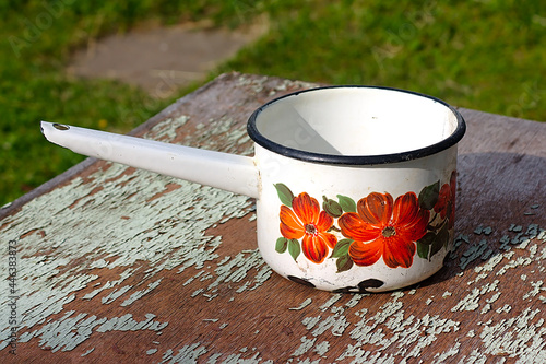 Fototapeta An enameled ladle on a worn countertop