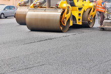 Pneumatic Steam Road Rollers Compact Fresh Asphalt On The Road In Front Of A Construction Site.