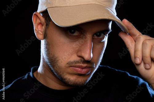 Fototapeta Retrato de estudio de joven con camiseta negra y gorra