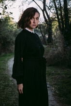 Unemotional Woman In Black Dress For Halloween Standing In Forest